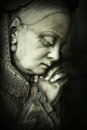 Suffering profile portrait of a beautiful sculpture of a elderly woman praying and crying Stock Images