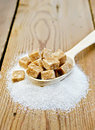Sugar brown and granulated sugar in a spoon on the board cubes of wooden white wooden table Stock Photography