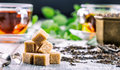 Sugar. Cane sugar. Cane sugar cubes heap close up macro shot. Tea in a glass cup, mint leaves, dried tea, sliced lime, cane brown Royalty Free Stock Photo