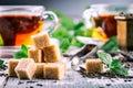 Sugar. Cane sugar. Cane sugar cubes heap close up macro shot. Tea in a glass cup, mint leaves, dried tea, sliced lime, cane brown Royalty Free Stock Photo
