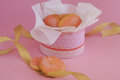 Sugar cookies in round box with golden tape on pink background frosting and gold decorative balls dotted white napkin near and Royalty Free Stock Photos