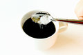 Sugar falling into black coffee in white cup Royalty Free Stock Photography