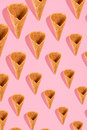 Sugar waffle cone for ice cream arranged in pattern on pink background. The image with copy space can be used as a Royalty Free Stock Photo