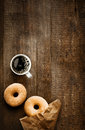 Sugared doughnuts and coffee on rustic wood overhead view of two tempting fresh with their brown paper wrapping a cup of strong Stock Image