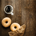 Sugared ring doughnut with espresso coffee close up overhead view of two delicious and crumpled brown paper packet on a rustic Royalty Free Stock Photo