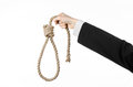 Suicide and business topic hand of a businessman in a black jacket holding a loop of rope for hanging on white isolated background Stock Photo