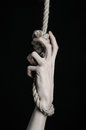 Suicide and depression topic human hand hanging on rope loop on a black background studio Stock Photos