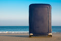 Suitcase on the beach a blue an empty with a quiet waterline and hardly any waves Stock Photography