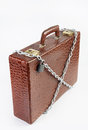 Suitcase is chained with a locked padlock made of crocodile leather Royalty Free Stock Photo