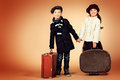 Suitcase in hand cute little boy and girl are standing with their old suitcases retro style Royalty Free Stock Images