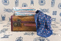 Suitcase maps and neckerchief are on the sofa geographic couch upholstered cloth with exotic pattern Stock Photos