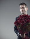 Suitor and roses man holding out large bouquet of red Stock Images