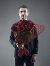 Suitor and roses shocked man holding out large bouquet of red Stock Image