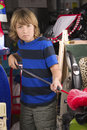 Sullen boy is dusting items stored in a messy full garage during spring cleaning Stock Images