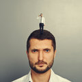 Sullen man with small man on the head over grey background Stock Photography
