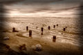 Sullivans island shoreline remnants of an old fishing pier along the at in sc a sailboat can just be seen along the horizon Stock Photography