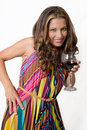 A sultry brunette with a glass of red wine in bright dress Stock Images