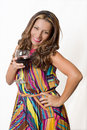 A sultry brunette with a glass of red wine in bright dress Stock Photography