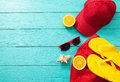 Summer accessories. Flip flops, sunglasses, towel, red cap and oranges on blue wooden background. copy space. Royalty Free Stock Photo