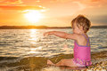Summer baby girl playing in sea at sunset Royalty Free Stock Photo