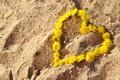 Summer background with dandelions in a heart shape on the sand Royalty Free Stock Photo
