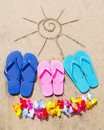 Summer background with flip flops and decoration on the sandy beach Stock Photos
