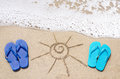 Summer background with flip flops on the sandy beach Stock Images
