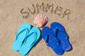 Summer background with flip flops seashell and sign on the sandy beach Stock Photos