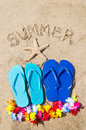 Summer background with flip flops starfish decoration and sign on the sandy beach Stock Photography