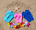Summer background with flip flops starfish decoration and sign vacation on the sandy beach Stock Photos