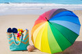 Summer background with rainbow umbrella and bag on the sandy beach Stock Image