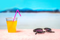 Summer background with yellow cocktail and sunglasses on towel on the beach. Beautiful blurred paradise ocean view. Royalty Free Stock Photo