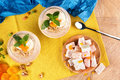 Summer banana smoothies in a huge glasses with Turkish Delight, dried apricots and walnuts on multi-colored background