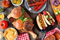 Summer BBQ food table scene with hot dog and hamburger buffet, top view over dark wood Royalty Free Stock Photo