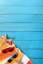 Summer beach border blue wood decking background copy space vertical scene with orange striped towel starfish and sunglasses on Stock Photos