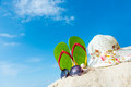 Summer beach green flip flop sunglasses and floppy hat at the Stock Image