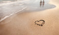 Summer beach love walk sunny sea sign on sand with wave and couple reflection neutral densitiy filter used to make blurry waves Royalty Free Stock Image