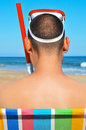 Summer on the beach view of back of a man wearing a diving mask and a snorkel Royalty Free Stock Photo