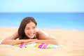 Summer beach woman sunbathing enjoying sun smiling lying down on towel looking away beautiful pretty cute multiracial asian Stock Photos