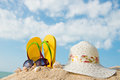 Summer at the beach yellow flip flop sunglasses and floppy hat Royalty Free Stock Image