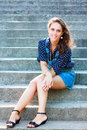 Summer beautiful girl portrait pretty young caucasian happy woman sitting on staircase Stock Photo