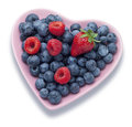 Summer berries heart food a shaped plate full of on a white background demonstrating a healthy diet Royalty Free Stock Images