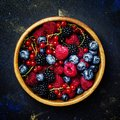 Summer berries in wooden bowl, black background, top view Royalty Free Stock Photo