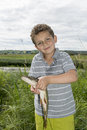 Summer boy stands near the lake and holding a big pike. Royalty Free Stock Photo