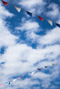 Summer bunting flags isolated against a cloudy blue sky Royalty Free Stock Photography