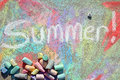Summer in chalk the word is written white sidewalk with a colorful background drawing and lots of scattered on the pavement Stock Photo