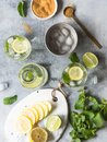 Summer citrus lemonade with ice in two bulging glasses, sugar in little white plate, slices of citrus on a ceramic white board and Royalty Free Stock Photo