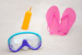 Summer close up of diving mask flip flops and suntan lotion b concept bottle on sandy beach Royalty Free Stock Images