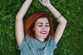 Summer close up portrait of pretty smiling young woman, laying on the grass, enjoy her vacation, natural make up red Royalty Free Stock Photo