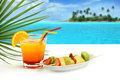 Summer cocktail and fruit skewers on exotic seascape Royalty Free Stock Image